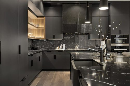 Ultra modern interior design in luxury kitchen with black cabinetry and granite countertops.