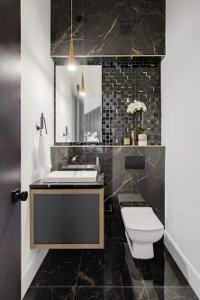 Ultra modern powder room with black marble tile and gold accents in Calgary home.