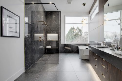 Luxury modern bathroom with black tile, glass shower, and chandelier by West Ridge Custom Homes.