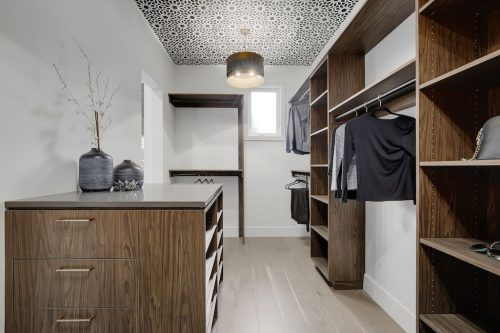 Walk-in closet with organizers, wallpaper accented ceilings by West Ridge Custom Homes.