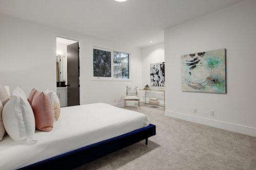 Simple modern bedroom with abstract art at home on Sovereign Crescent in Calgary.