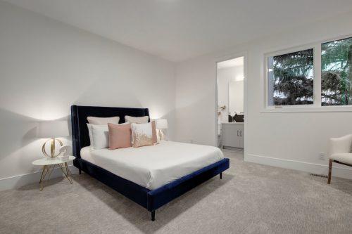 Bedroom with blue velvet bed in custom home in Scarboro Calgary for sale by Plintz Real Estate.