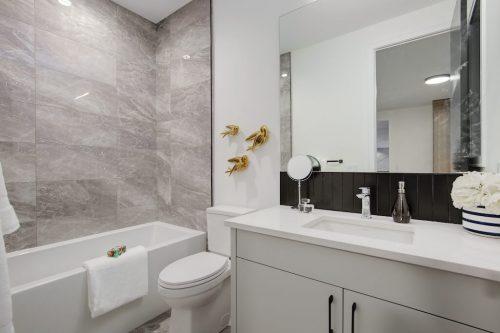 Modern bathroom with grey tile, bathtub, and black accent tile.