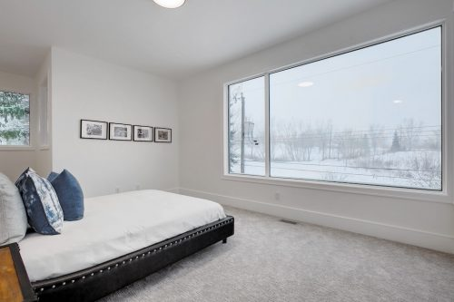 Luxury bedroom with large window overlooking the Bow River in Calgary.
