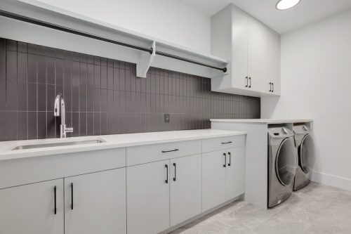 Luxury laundry room with storage and front loading washer and dryer.