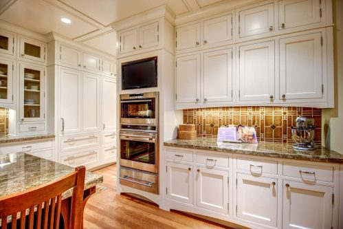 White Empire Custom Home with built-in ovens, granite counters, and decorative tile backsplash.