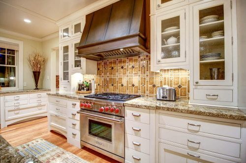 Empire Custom Homes kitchen with Wolf range, industrial hoodfan, and decorative tile.