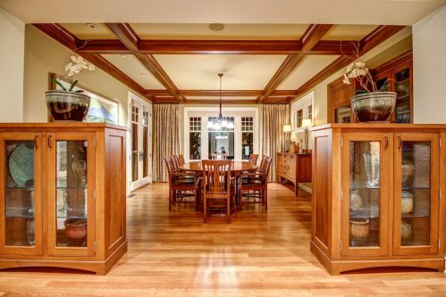 Dining room with open wood beams coffered ceiling with hardwood floors.