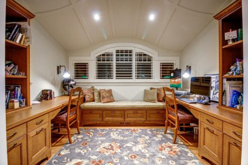 Side-by-side built-in desks and window seat in bonus room with barrel ceiling.