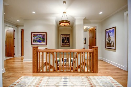 Upstairs foyer with dual staircase and chandelier.
