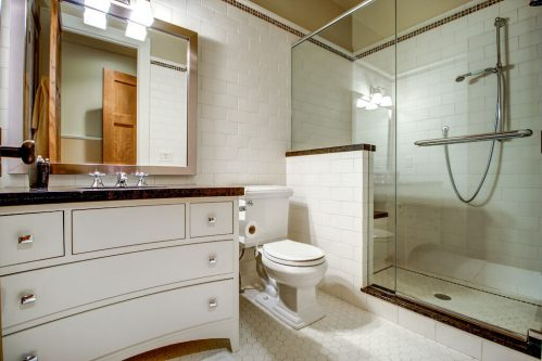 Bathroom with subway tile, glass shower, and curved vanity.