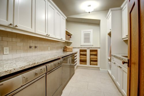 Luxury laundry room with dual washer and dryers and storage in Rideau Park Calgary home.