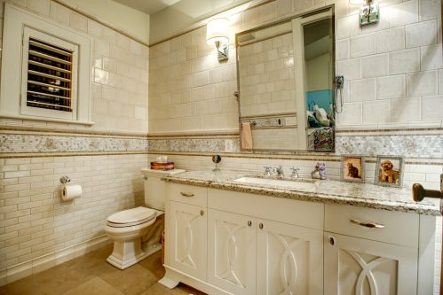 Empire custom bathroom with subway tile and granite vanity in Rideau Park home for sale by Plintz Real Estate.