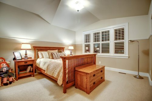 Rideau Park Calgary home bedroom with vaulted ceilings and shutter windows.