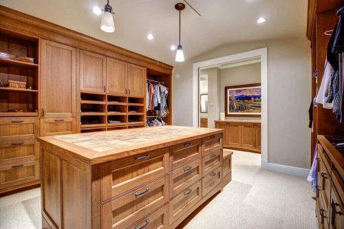 Walk-in closet with organizer and centre island with ample storage.