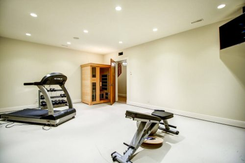 Luxury home basement gym with treadmill, weight bench, and sauna.