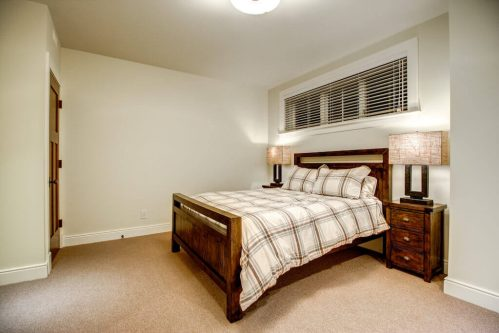 Basement bedroom with wood bed frame and night stand in Rideau luxury home.