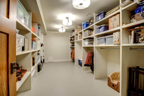 Storage room with shelving on both sides in Calgary home.
