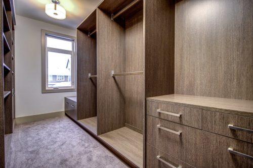 Walk-in closet with closet organizers in Empire Custom Luxury townhome in Valour Park Calgary.