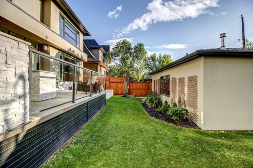 Back deck and detached garage of luxury Elbow Park Calgary home.