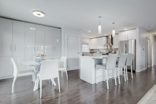 Renovated bungalow with hardwood floors and white cabinet and island.