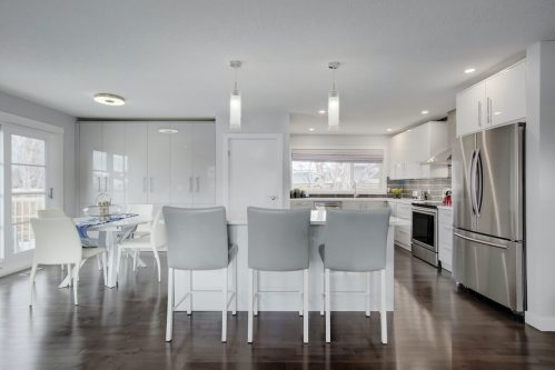 Modern white kitchen with gloss cabinets and grey stools in renovated bungalow.