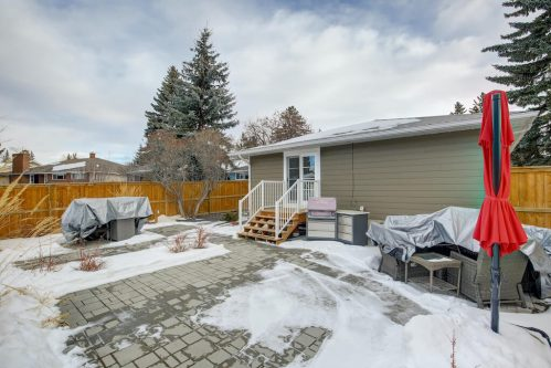 Paving stone patio of Glenbrook Calgary Bungalow in winter with snow.