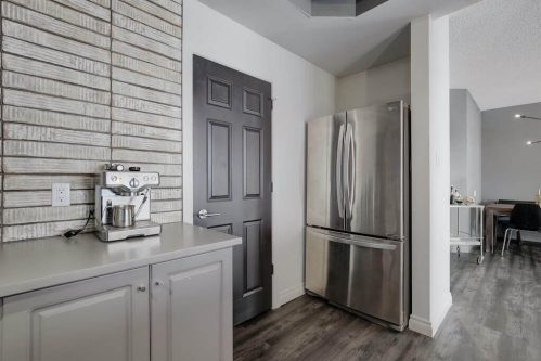 Condo kitchen with stainless steel refrigerator and espresso machine.