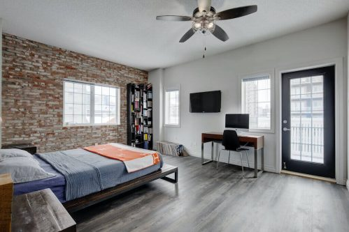 Loft bedroom with exposed brick wall and ceiling fan and patio in Beltline.