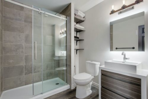 Modern bathroom with grey vanity and glass shower.