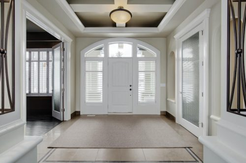 Grand entry with arched white door of home by architect Dean Thomas at 8 Villosa Ridge Drive in Calgary.
