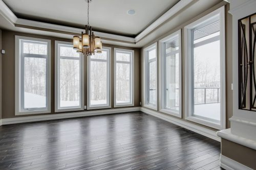 Dining room with floor to ceiling windows with view or trees in Calgary winter.