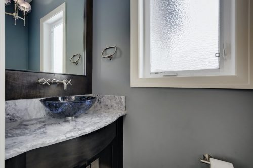 Powder room with marble vanity and blue vessel sink at 8 Villosa Ridge Drive.