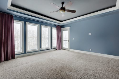 Blue master bedroom with inset ceiling, large windowns, and patio doors.