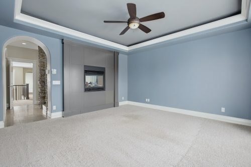 Master bedroom with blue walls, inset ceiling, fan, and double sided fireplace to ensuite bathroom.