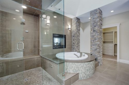 Luxury ensuite bathroom with large glass steam shower, round soaker tub, stone accents and fireplace. Luxury home for sale by Plintz Real Estate.