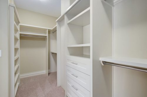 Walk-in closet with organized storage in Springbank acreage.