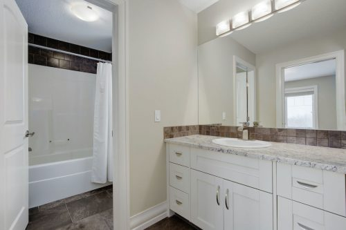 Luxury ensuite bathroom with white cabinetry and marble countertops in Calgary luxury home.