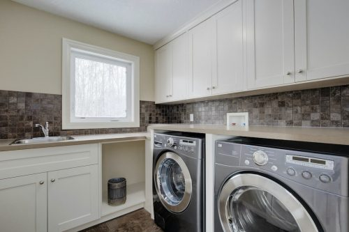 High end front loading washer and dryer in luxury laundry room with storage at 8 Villosa Ridge Drive Springbank.