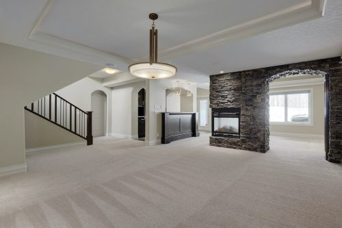 Acreage walkout basement with rec room, stone fireplace and bar at 8 Villosa Ridge Drive in Springbank Calgary.