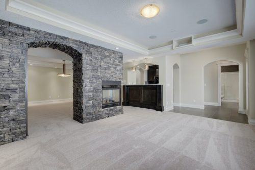 Walkout basement with rock archway and fireplace in Springbank Calgary acreage home for sale by Plintz Real Estate.
