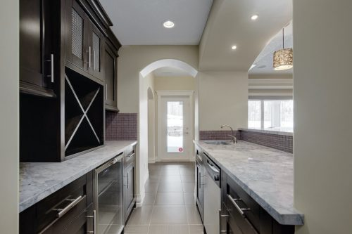 Luxury kitchen with dark cabinetry and granite countertops of Calgary acreage home.
