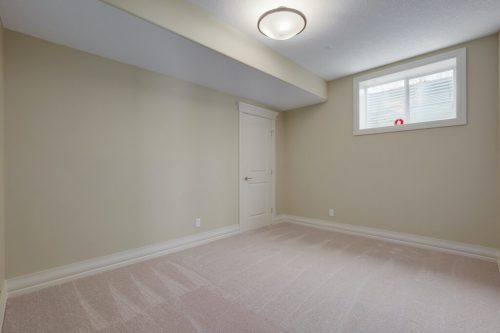 Basement bedroom with neutral walls and carpet in acreage home.