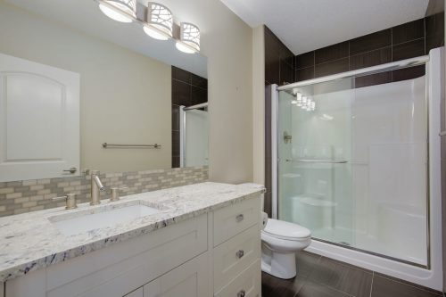 Bathroom with glass shower and white and granite vanity at 8 Villosa Ridge Drive in Springbank Calgary.