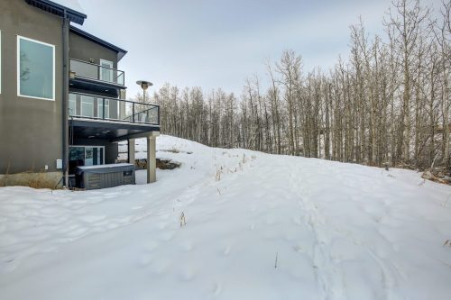 Treed view from balcony and walkout patio of home at 8 Villosa Ridge Drive in Springbank Calgary.