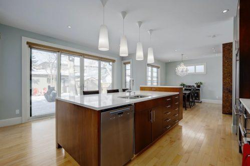 kitchen-island-hardwood-open-concept-patio-doors-pendnat-lights-3119-Kilkenny-Drive-SW-Killarney-Calgary-Real-Estate-Homes-For-Sale-Plintz-Realtor-Dennis