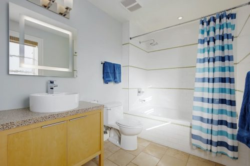 bathroom-tub-blue-stripe-shower-curtain-3119-Kilkenny-Drive-SW-Killarney-Calgary-Real-Estate-Homes-For-Sale-Plintz-Realtor-Dennis