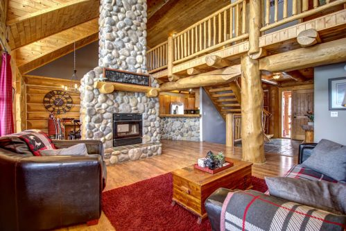 Great-room-stone-fireplace-vaulted-ceilings-timber-beams-wood-plank-107-Signal-Hill-Point-SW-Home-For-Sale-Plintz-Real-Estate-Walkout-Basement-Realtor-Dennis