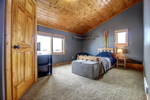 vaulted-ceilings-blue-bedroom-107-Signal-Hill-Point-SW-Home-For-Sale-Plintz-Real-Estate-Walkout-Basement-Realtor-Dennis