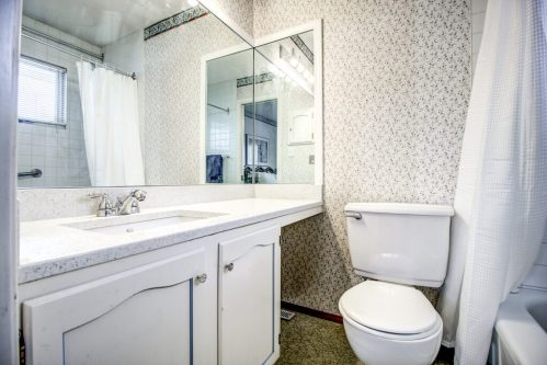 Retro bathroom with wallpaper and white vanity in bungalow in home for sale by Plintz Real Estate in Calgary Alberta.